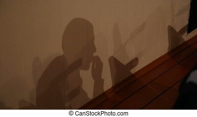 Shadow on the wall of the sitting man