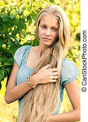 Portrait of beautiful young girl with long blond hair in...
