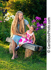 Beautiful blond young girl with her little sister in the...