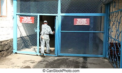 The guard passes through the gates of the prison
