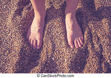 The feet of a young woman standiing on a shingle beach