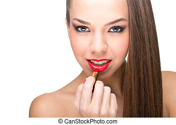 Beautiful fair skinned woman using a red lipstick