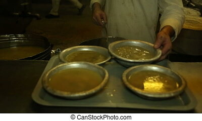 A cook pours soup in the iron plates