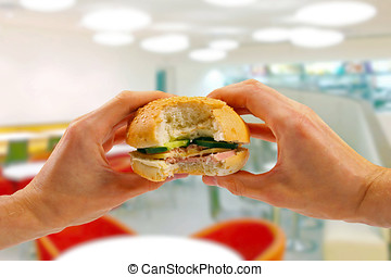 hands hold a burger in fast food restaurant