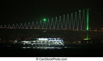 urban transport by sea in front Bosporus Bridge at night