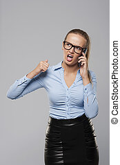 Angry businesswoman shouting into the mobile phone