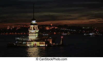 Maiden Tower and passenger ship at night time