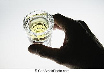 Hand around shot glass of liquor