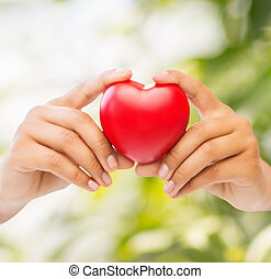 woman hands with heart - health and charity concept - close...