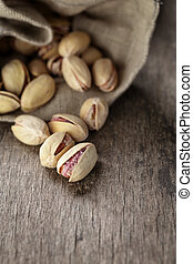 roasted and salted pistachios pour out of the bag, rustic...