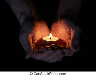 adult man hands holding burning candle