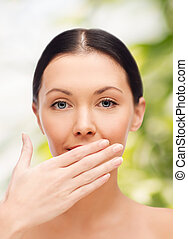 beautiful woman covering her mouth - spa, health and beauty...