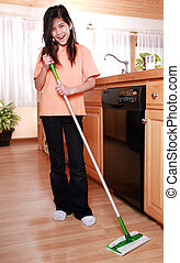 Girl mopping kitchen floor - Girl happily mopping kitchen...