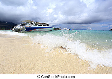 Speed boat anchored on beautiful sand beach