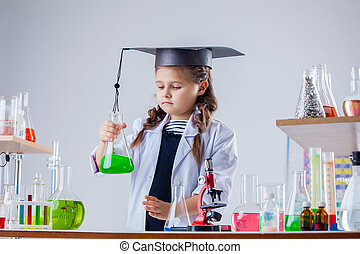 Concentrated little girl posing in chemistry lab, close-up