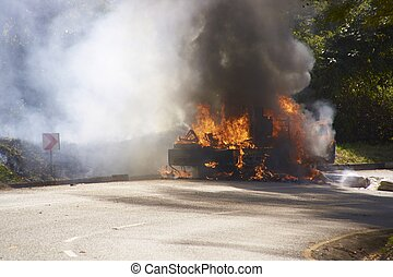 Burning Vehicle - Smoke and flames billowing from a burning...