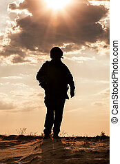 Silhouette of young soldier in military helmet against the...