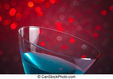 detail of one glass blue cocktail on red tint light background