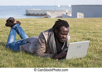 Young student with laptop - Young student accessed the...