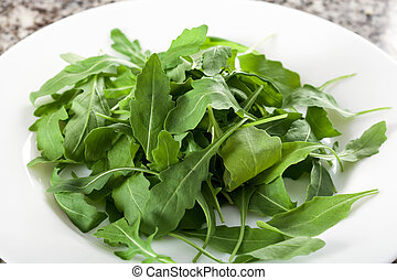 Plate with salad rocket leaves - A white plate full of fresh...