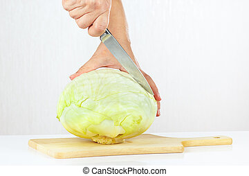 Hand with a knife cuts cabbage on a white background