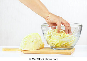 Hand mixes shredded cabbage in a glass bowl on a white...