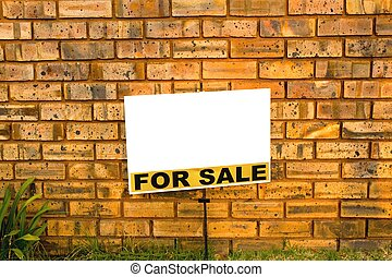 for sale sign in front of a brick wall