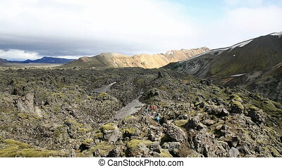 moss-covered lava fields in Landmannalaugar - Tourists...