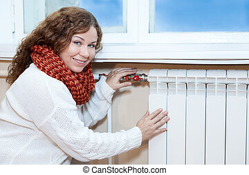 Woman in warm clothes checking the temperature of heating...