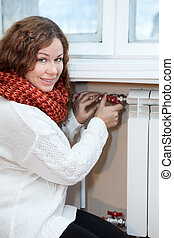 Woman in warm clothes controling the temperature of heating...