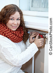 Woman controling the temperature of heating radiator in...
