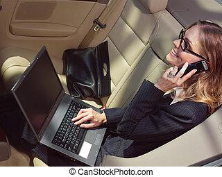 businesswoman has a fan with laptop in black car