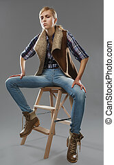 androgynous girl sits on a chair. Jeans and jacket.