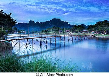Country bridge across Nam Song river, Vang Vieng, Laos. -...