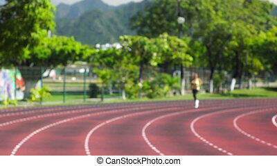 Running a Stadium track - A young woman running at a track...