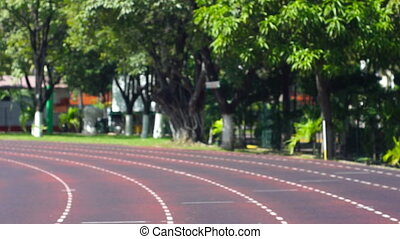 Running the stadium track - A young woman running at a track...