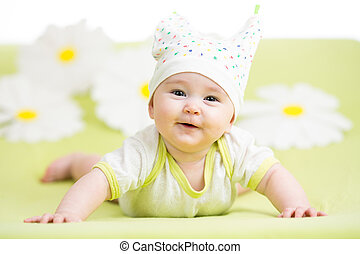 smiling cute baby lying on green