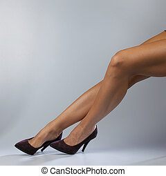 Sexy legs - Sexy woman\'s legs isolated on gray background