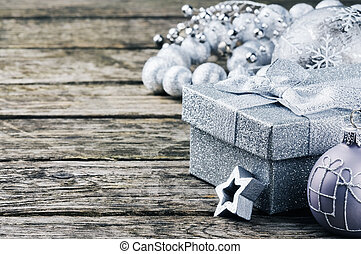 Christmas gift box and ornaments in silver tone on wooden...