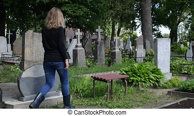 woman depressed cemetery - Depressed woman sit on bench near...