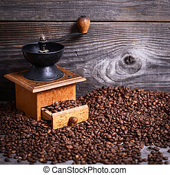 Manual coffee grinder with beans on wooden background