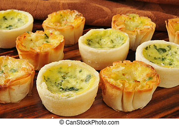 Assorted mini quiche on a wooden cutting block