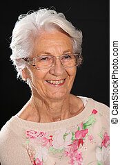 Smiling white haired grandmother posing on a dark background