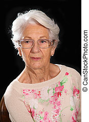 White haired grandmother posing on a dark background