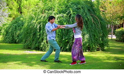 Young couple dancing in park