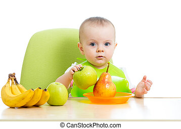 baby eating healthy solid food fruits - baby girl eating...