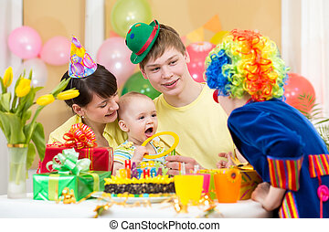 baby girl celebrating first birthday with parents and clown