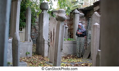 Muslim girl praying in small graveyard