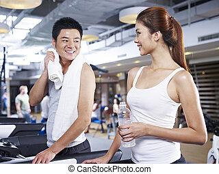 man and woman on treadmill - young man and woman talking...