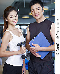 man and woman in gym - portrait of young man and woman in...